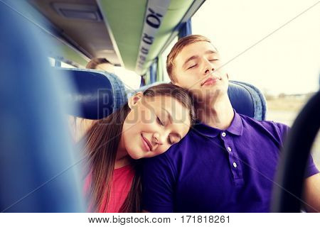 transport, tourism, road trip and people concept - happy teenage couple or tourists sleeping on shoulder in travel bus
