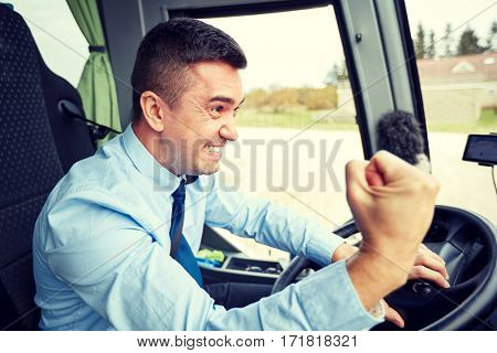 transport, tourism, gesture, emotion and people concept - angry driver showing fist and driving bus