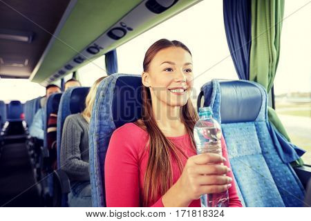 transport, tourism, road trip and people concept - happy young woman with water bottle in travel bus