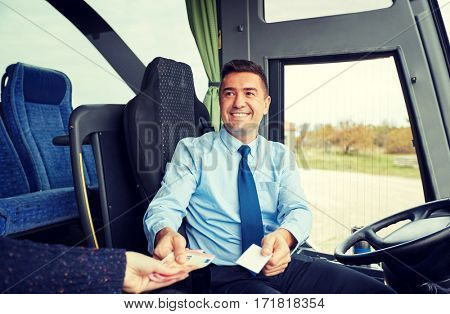 transport, tourism, road trip and people concept - smiling bus driver selling ticket and taking money from passenger