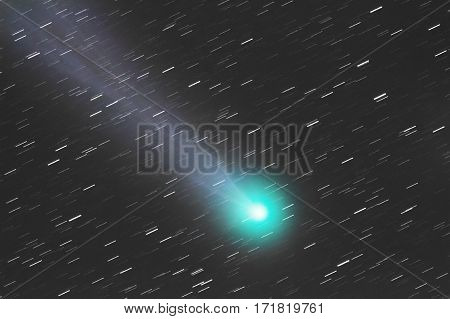 Comet with tail and green core flying though space.