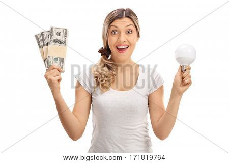 Delighted woman holding bundles of money and a LED light bulb isolated on white background