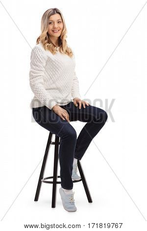 Pretty woman sitting on a chair smiling and looking at the camera isolated on white background
