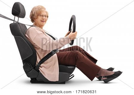 Elderly woman seated in a car seat holding a steering wheel and looking at the camera isolated on white background