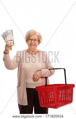 Happy mature woman holding bundles of money and an empty shopping basket isolated on white background