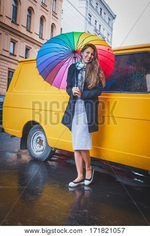 Girl With Long Hair Standing Under A Bright Colored Umbrella And Smiling Against The Background Of