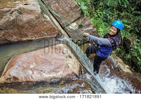 Beaufort,Sabah,Malaysia-Jan 28,2017:Happy muslim girl ready to abseil down a waterfall in Beaufort,Sabah,Borneo.Waterfall Abseiling activity adventure getting famous in Sabah,Malaysia.