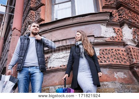 Man And Woman Holding Umbrellas In A Windy Day Laughing Against The Backdrop Of An Old House