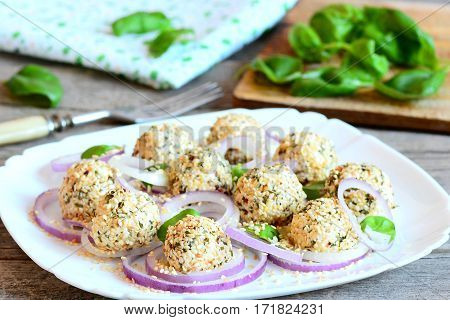 Cheese balls appetizer. Delicious cheese balls with dried herbs and roasted sesame seeds served with onion rings and basil on a plate. Easy and quick appetizer recipe. Rustic style