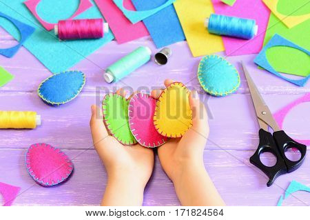Child holding a felt Easter eggs in his hands. Little child made Easter crafts of felt. Tools and materials for needlework on wooden table. Simple kids crafts concept