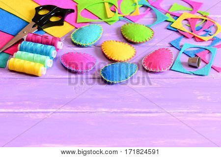 Colorful felt Easter eggs decorations, felt sheets and scraps, scissors, thread, thimble on a table. Easy Easter sewing crafts idea for kids. Easter craft background with copy space for text