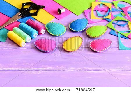 Multicolored felt Easter eggs crafts, felt sheets and scraps, scissors, thread set, thimble on a table. Simple Easter sewing crafts for children. Easter handicraft background with copy space for text