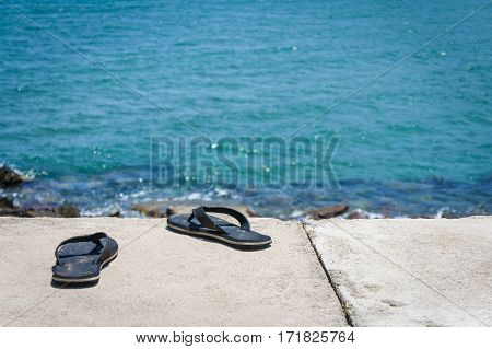 men's sandals on the concrete promenade by the sea.
