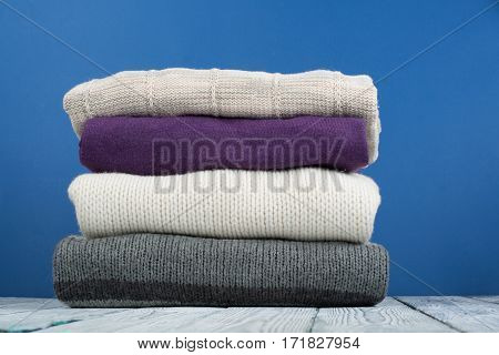 Knitted wool sweaters. Pile of knitted winter autumn clothes on blue wooden background sweaters knitwear space for text