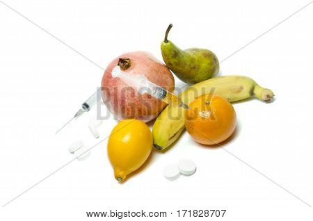 Needle and syringe injected in the fruit. Nutrition concept. Enhanced fruits. GMO. Healthy life versus unhealthy life. Fruits and pills on the white background