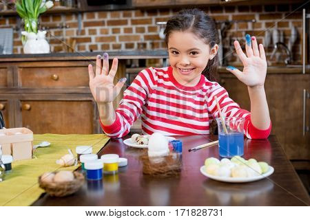 Cute smiling girl showing palms in paint while painting easter eggs