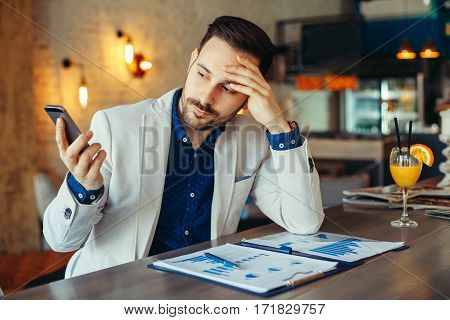 Young businessman looking at phone in cafe