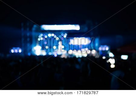 Silhouettes of de-focused concert crowd with stage lights