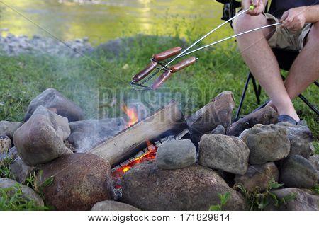 man roasting hotdogs on campfire near river