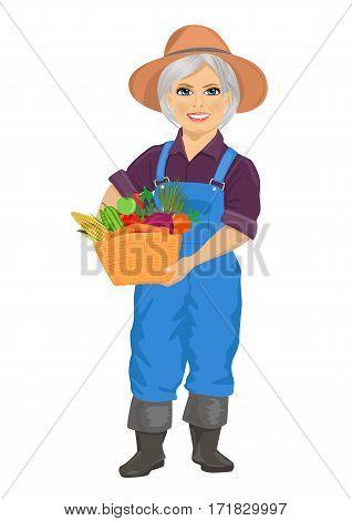 elderly female gardener wearing overalls holding a basket of fresh vegetables