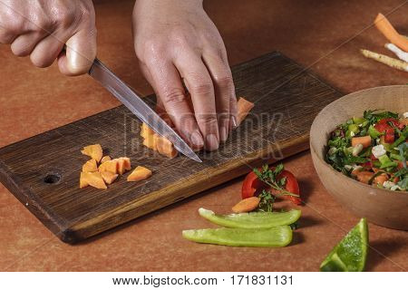 Chef chopping vegetables on a kitchen board