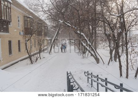 People walk on a snow-covered street during a blizzard.