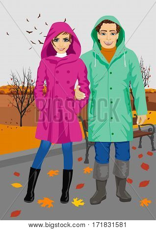 young couple wearing raincoats standing in the park in autumn