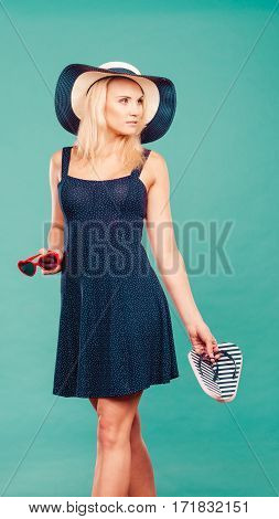 Summer trendy fashionable outfit ideas concept. Woman wearing short navy dress sun hat holding flip flops and sunglasses.