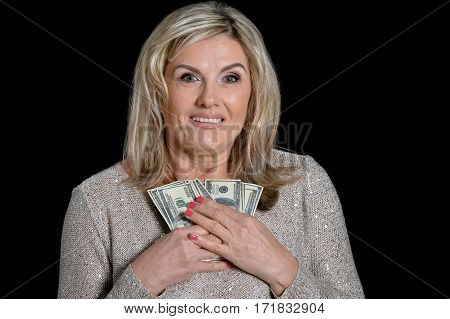 mature woman with money on black background
