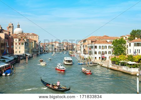 VENICE,ITALY-June 30, 2016.Tourists on water street with Gondola in Venice. its entirety is listed as a World Heritage Site, along with its lagoon.June 30, 2016 VENICE,ITALY
