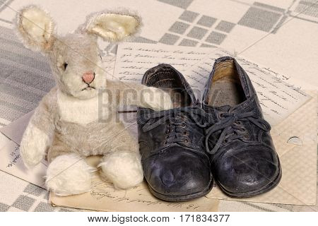 Remembrance of Childhood Concept: Vintage Toy Bunny and Children's Shoes