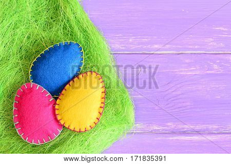 Pink, yellow and blue felt Easter eggs in a grass of green sisal fibre and on purple wooden background with copy space for text. Vivid Easter background. Closeup