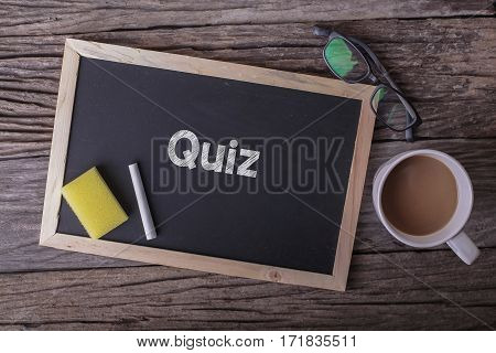 Quiz On Blackboard With Cup Of Coffee, With Glasses On Wooden Background.