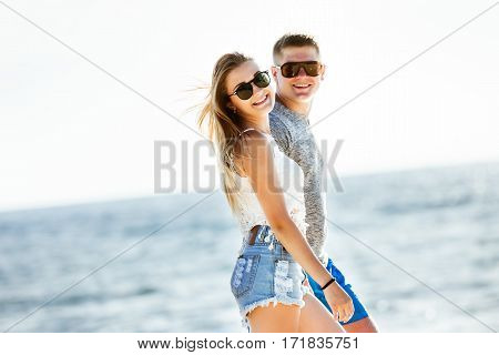 Happy couple is walking on the beach on background of sea
