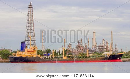 Oil refinery river front with transport ship industrial background