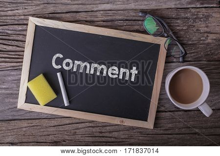 Comment On Blackboard With Cup Of Coffee, With Glasses On Wooden Background.