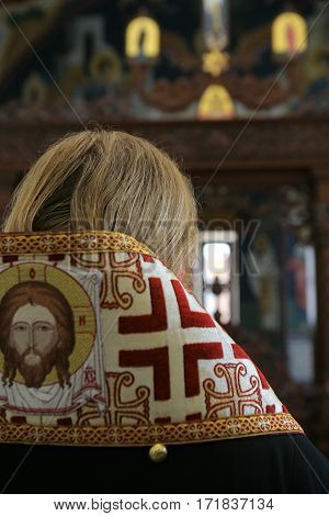 Orthodox bishop praying in front of altar icons