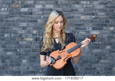 Woman Looking At Violin In Her Hands