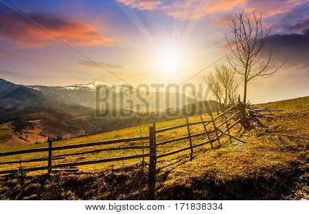 Wooden Fence Along The Path In Mountains At Sunset