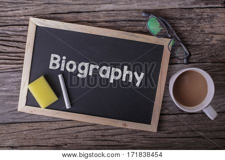 Biography On Blackboard With Cup Of Coffee, With Glasses On Wooden Background.