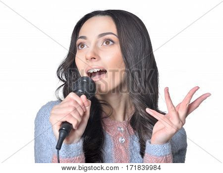 young woman singing in microphone on white