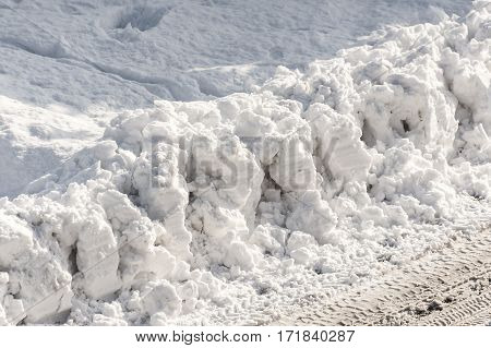Detail of big parts of ploughed fresh snow on side of a road
