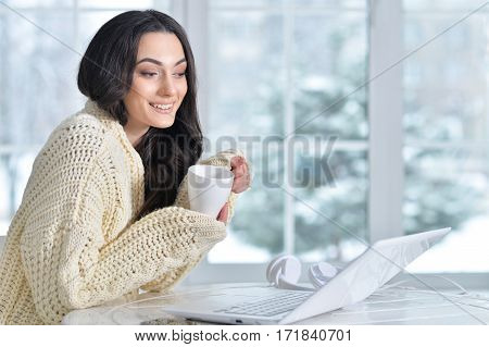 excited young woman using laptop and drinking tea