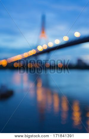 Abstract blurred lights Suspension bridge with reflection at twilight