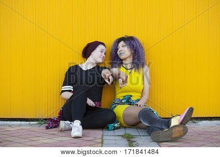 Young interracial teen girlfriends  isolated on yellow background