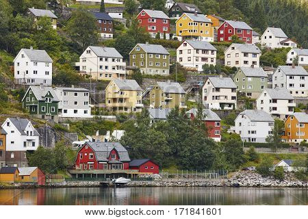 Traditional norwegian fjord village with colored houses forest and harbor.