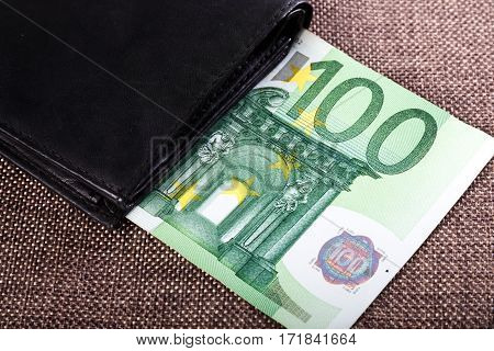 Banknotes of hundred euros sticking out of black wallet closed on burlap background. Money in cash. Closeup image.