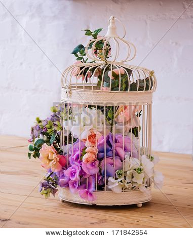 Birdcage with colored flowers standing on wooden floor