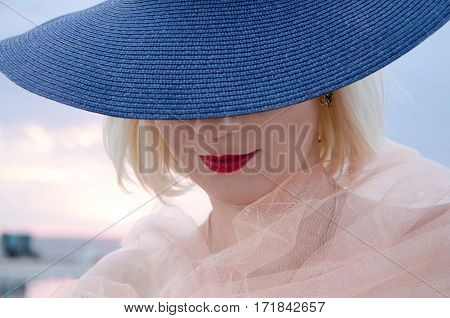 Young woman with red lips in a hat wearing neckerchief on sunset