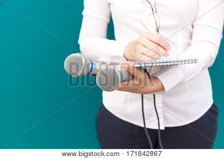 Female reporter or journalist writing notes at news conference